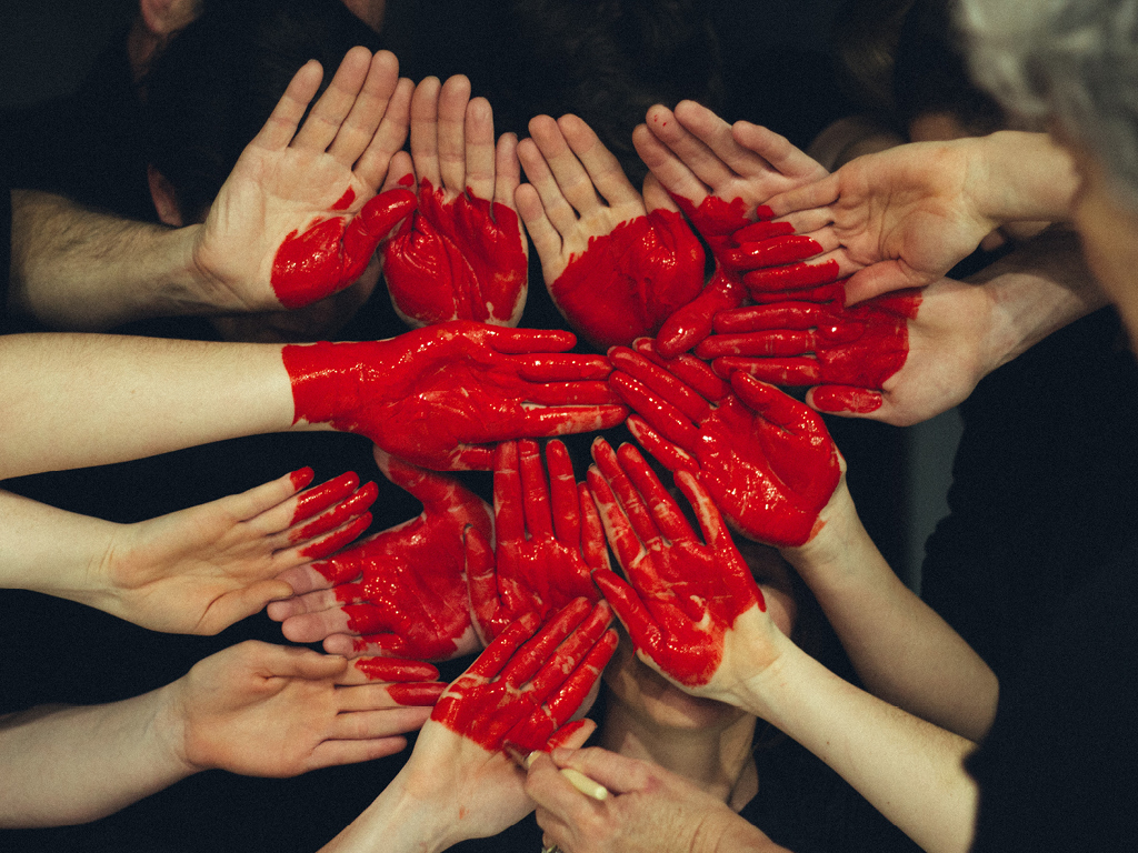 People with hand together forming painted red heart