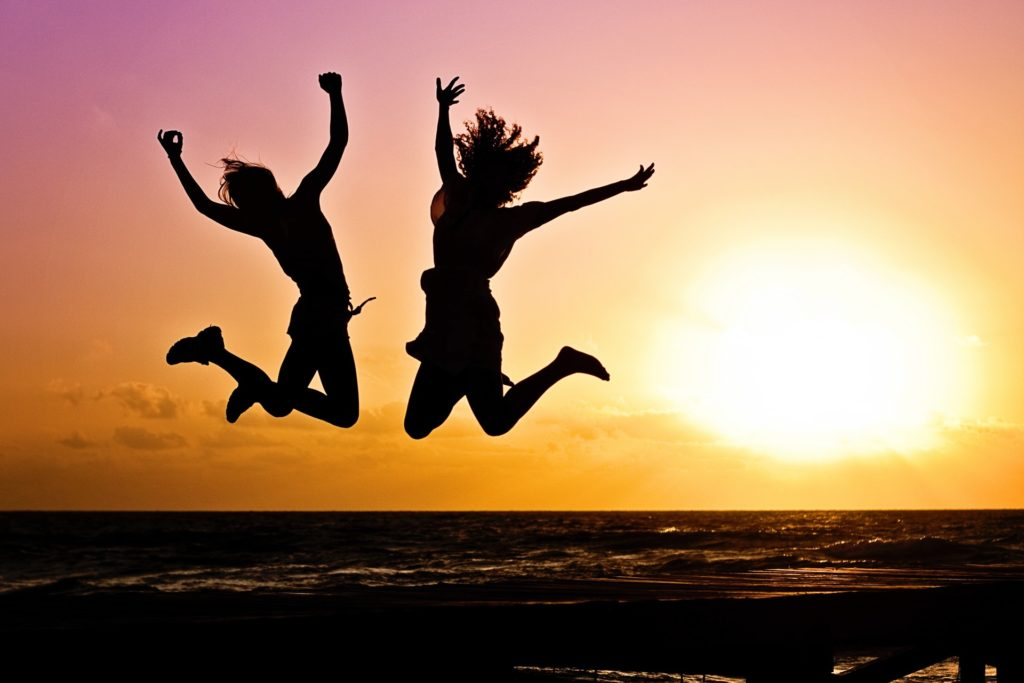 silhouette of 2 young people jumping with sunset in background