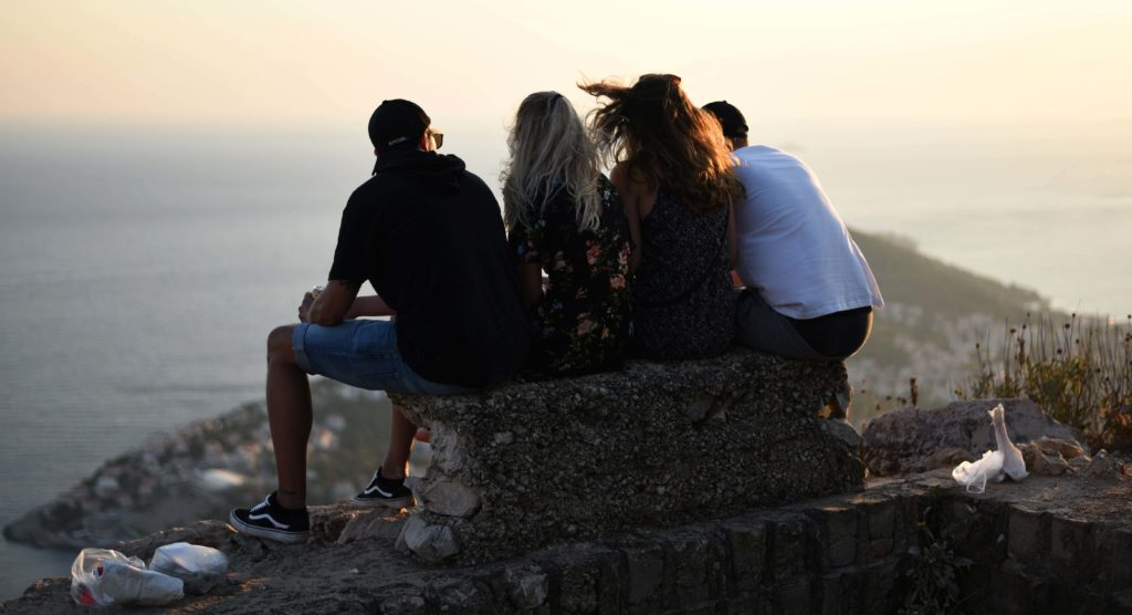 image of people sitting together on a rock